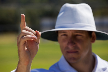 Umpire gesturing out sign during match on sunny day Stock Photo