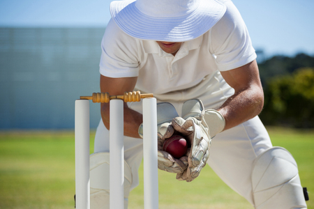 Wicketkeeper catching ball behind stumps on sunny day
