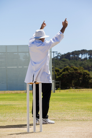 Full length of cricket umpire signalling six runs during match on sunny day against clear sky