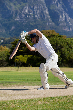 Cricket player playing on field against mountain during sunny day Stock Photo