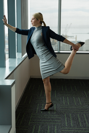Executive performing stretching exercise near window in office Stok Fotoğraf