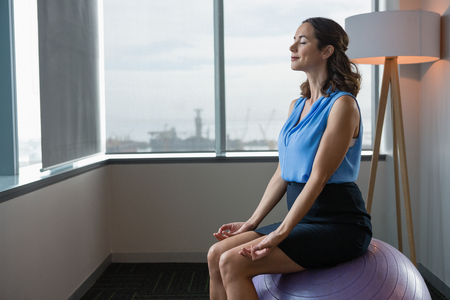 Executive meditating on fitness ball in office Stock Photo