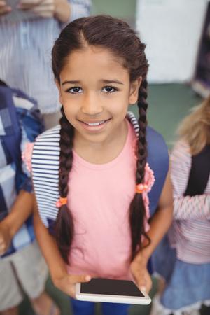 Portrét roztomilá dívka stojící s digitální tablet ve škole