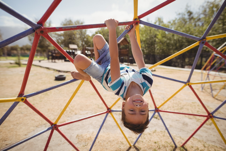 Portrait of happy schoolboy playing on dome climber at school playground