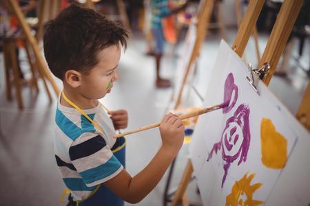 Aandachtige schooljongen die op doek panting maakt tijdens het tekenen van de klas Stockfoto