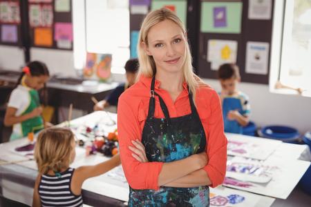 Portret van lachende leraar staande met armen gekruist in teken klasse Stockfoto