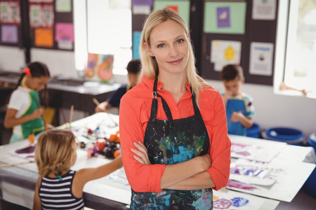 Portrait of smiling teacher standing with arms crossed in drawing class