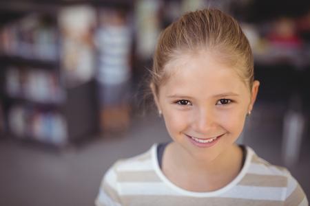 Portret van lachende schoolmeisje in de bibliotheek op school Stockfoto