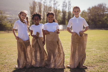 Portrait of happy schoolgirls standing in sack during race on a sunny day