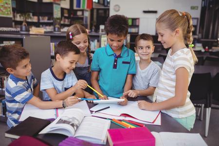 Attentive schoolkid using digital tablet in library at school
