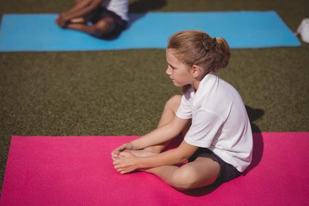 premises: Attentive schoolgirl exercising in schoolyard Stock Photo