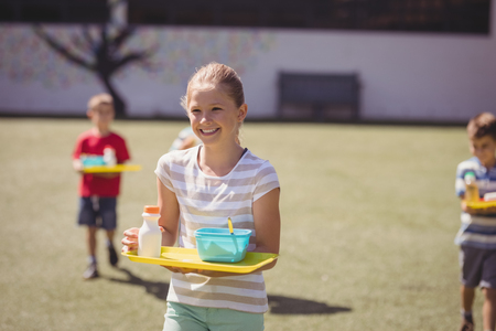 Happy schoolgirl holding meal in tray at school