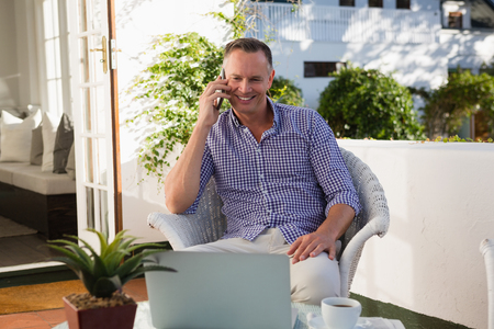 Mature businessman talking on phone while sitting by laptop in outdoor cafe