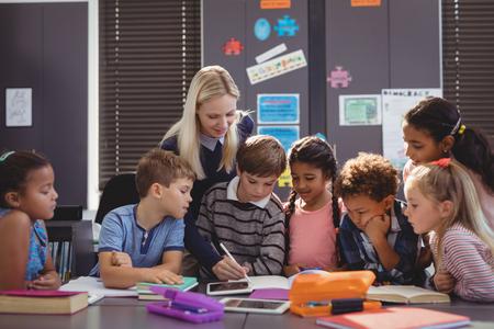 Teacher helping schoolgirl with her homework in classroom at school Stock Photo - 79230071