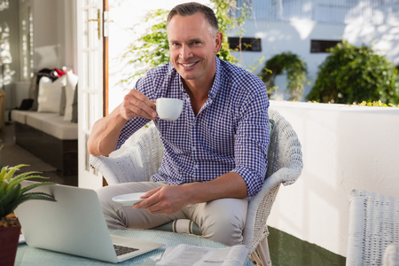 Portrait of mature businessman drinking coffee while sitting by laptop in outdoor cafe Stock Photo