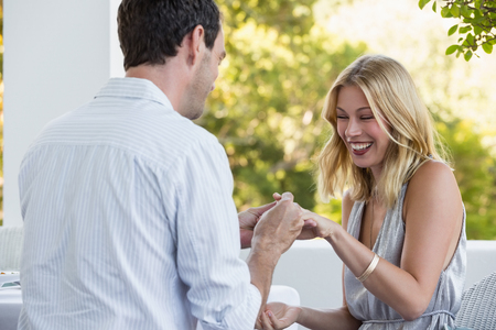 astonishing: Rear view of man putting ring on woman finger at restaurant