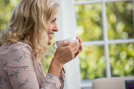Side view of smiling businesswoman holding coffee cup in cafe Stock Photo