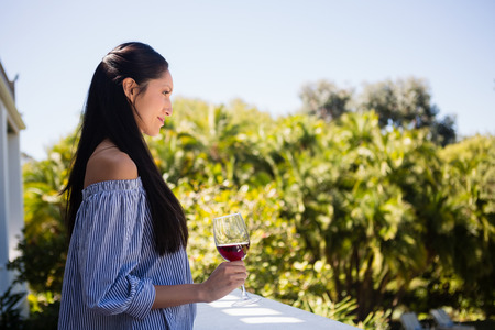 Side view of pretty woman holding red wine glass in restaurant