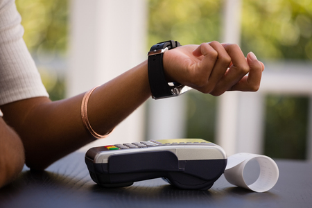 Mid section of woman making payment with smart watch and card reader in cafe Stock Photo - 79257565