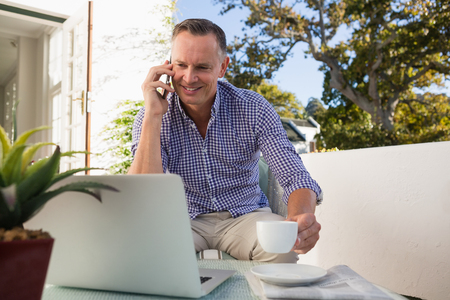 Smiling mature businessman talking on phone while having coffee in outdoor cafe