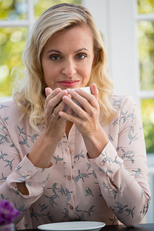 Portrait of confident businesswoman holding coffee cup in cafe