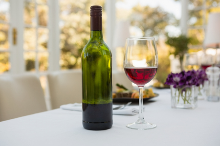 Close up of wineglass and bottle on table in restaurant