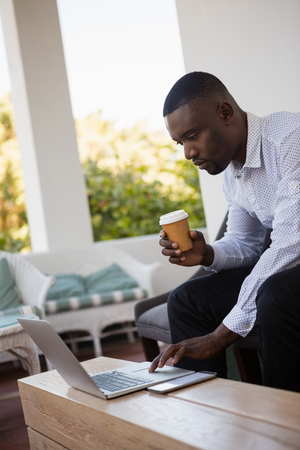 Focused businessman holding disposable coffee cup while using laptop at cafe Stock Photo