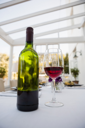 Close up of red wine and bottle on table in restaurant Stock Photo