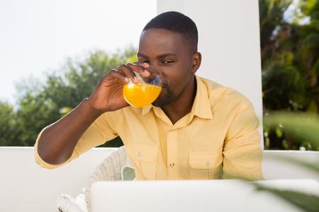multi tasking: Young man drinking orange juice while looking at laptop in cafe Stock Photo
