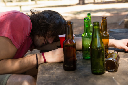 Drunk man leaning on the table holding a glass in the park
