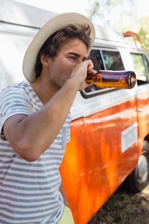 若い男が公園で瓶からビールを飲む