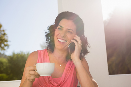 Smiling young woman talking on mobile phone while holding coffee cup at cafe