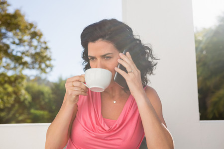 Young woman drinking coffee while talking on mobile phone at cafe Stock Photo