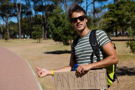 Man hitchhiking at roadside on a sunny day Stock Photo