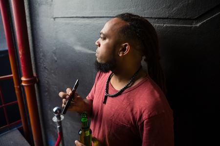 injurious: Man smoking electronic cigarette at the entrance of bar