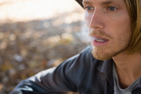Thoughtful man exhaling smoke in the park Stock Photo