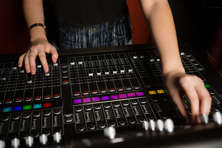 Mid-section of female audio engineer using sound mixer in recording studio
