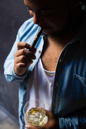 joven fumando: Man smoking while having whisky at the entrance of bar