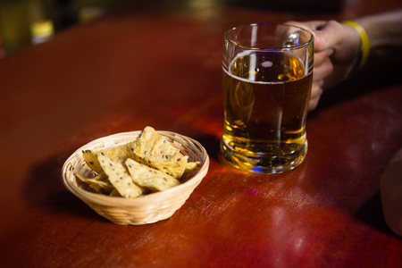Close-up of mans hand holding a mug of beer with snack at bar counter