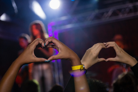 Hands of audience forming heart shape during stage show in nightclub