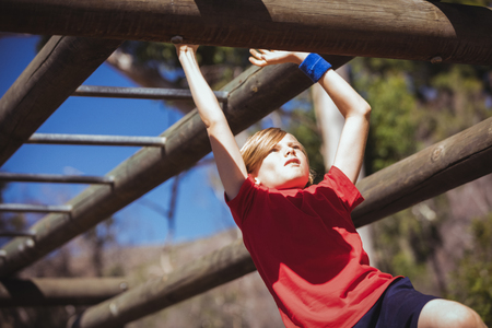 Girl climbing monkey bars during obstacle course training in the boot camp