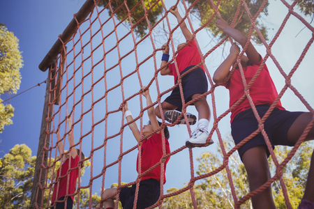 Kids climbing a net during obstacle course training in the boot camp