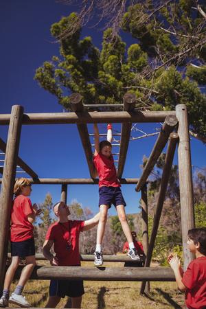 Trainer assisting girl to climb monkey bars during obstacle course training in the boot camp