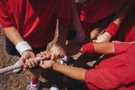 Kinder, die Tauziehen während des Hindernislauftrainings im Ausbildungslager spielen