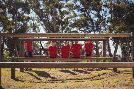 Trainer instructing kids during obstacle course training in the boot camp Stock Photo