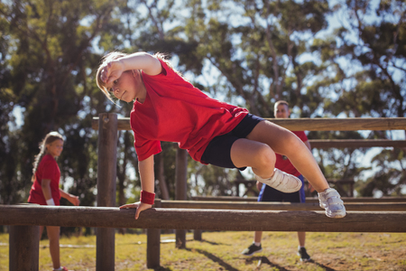 Kids jumping over the hurdles during obstacle course training in the boot camp Stock Photo