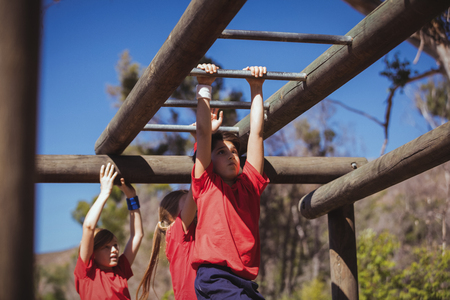 Kids climbing monkey bars during obstacle course training in the boot camp Stock Photo