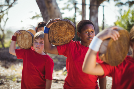 Kids carrying wooden log during obstacle course training in the boot camp Stock Photo