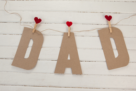 Close up of text dad with heart shapes on wooden table