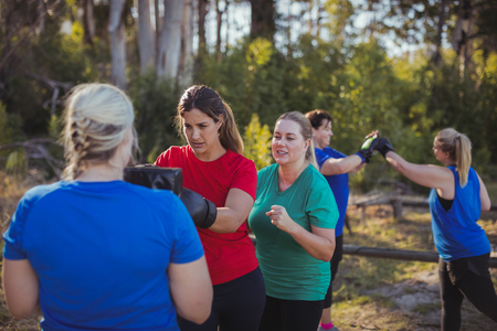 Woman practicing boxing in the boot camp on a sunny day